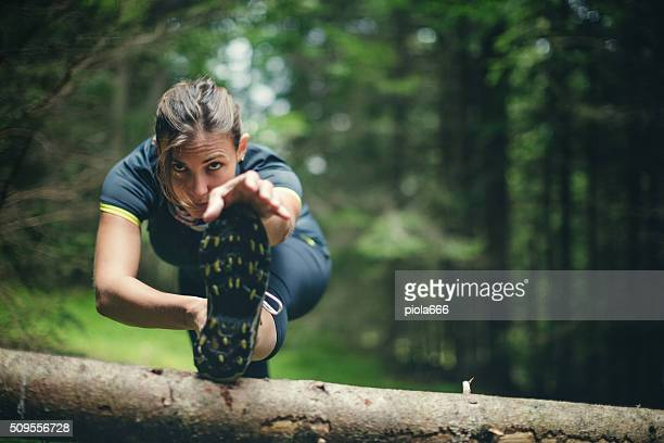 woman athlete stretching in the forest after running - cross country running stock pictures, royalty-free photos & images