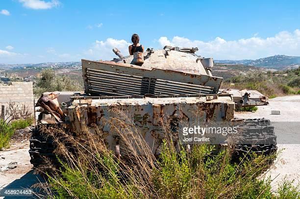 Woman atop rusting tank in Qana, Lebanon
