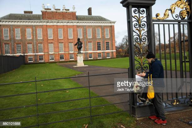 A woman attaches a card addressed Prince Harry and Meghan Markle to the gates outside Kensington Palace following the announcement of the couple's...