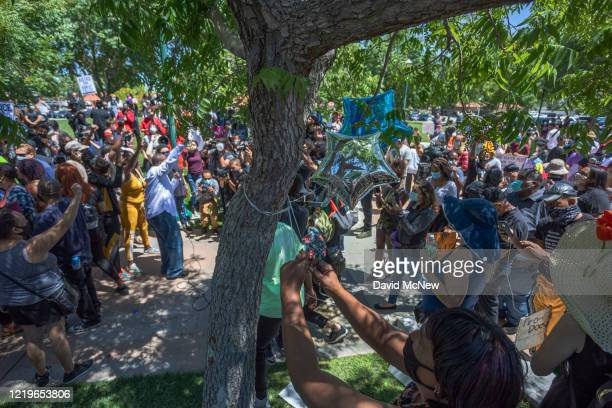 A woman attaches balloons to the tree that authorities say Robert Fuller a 24yearold black man was found hanging dead from near Palmdale City Hall as...