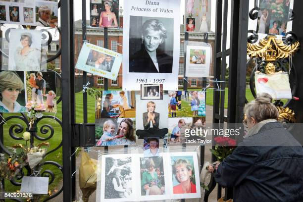 A woman attaches flowers among photographs and messages to an entrance gate to Kensington Palace ahead of the 20th anniversary of the death of Diana...