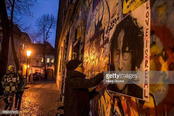 A woman attaches the placard with picture of John Lennon on the Lennon Wall the memorial dedicated to the late John Lennon on the 35th anniversary of...