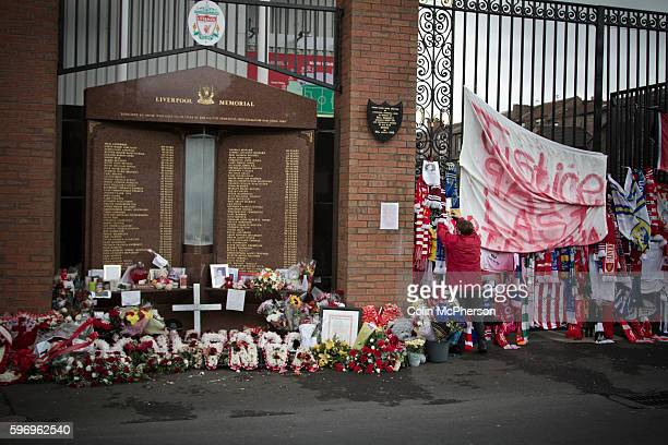 A woman attaching a scarf to the Shankly Gates next to the memorial at Anfield to the 1989 Hillsborough stadium disaster where 96 Liverpool football...