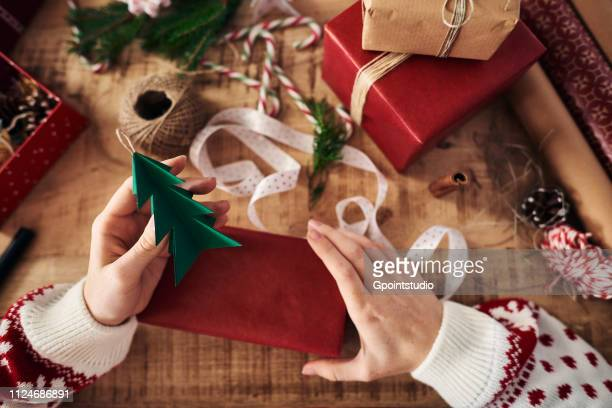 Woman attaching Christmas tree shaped decoration on Christmas present