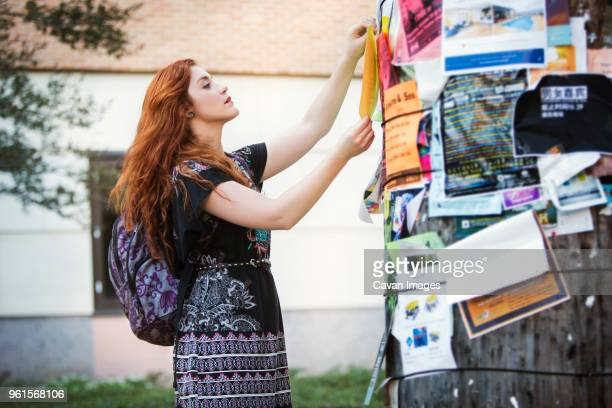 Woman attaching poster on wall at campus