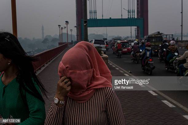 A woman attempt to protect themselves from the haze as walk at Ampera bridge on October 3 2015 in Palembang South Sumatra Indonesia The air pollution...