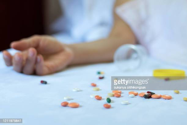 woman attempting suicide with pill overdose. - suicide stock pictures, royalty-free photos & images