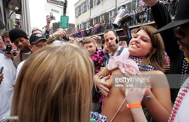 A woman attempts to cover her breasts after exposing them on Bourbon Street as men look on during Mardi Gras festivities February 8 2005 in New...