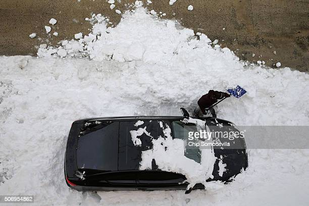 A woman attempts to dig her car out from underneath nearly 20 inches of snow in the Columbia Heights neighborhood following the weekend blizzard...