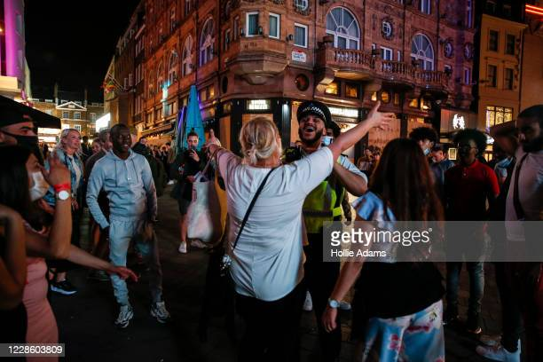 Woman attempts to hug a Met Police officer in Leicester Square on September 19, 2020 in London, England. The British government reported 4,422...