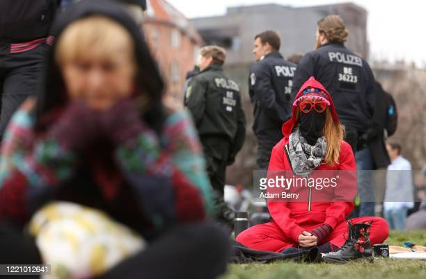 Woman attempts to show she is peaceful by meditating as she demonstrates against restrictions on public life designed to stem the spread of the...