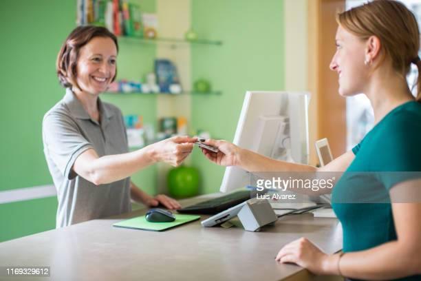 woman attending customer at dental pharmacy - arzthelferin stock-fotos und bilder