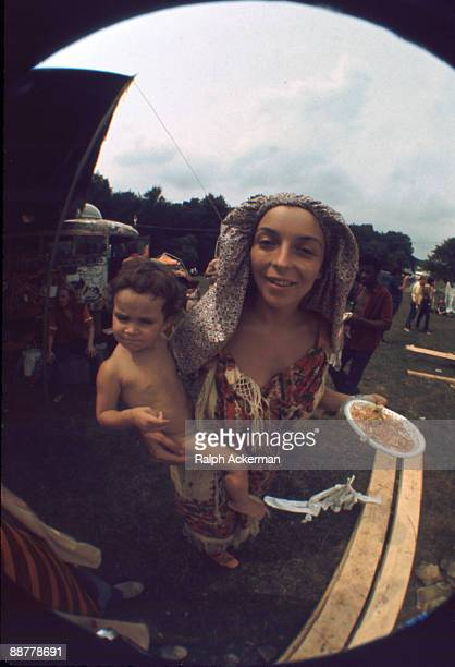 A woman attending the Woodstock Music Festival holds a plate of food in her left hand while carrying her young son in her right arm Bethel NY August...