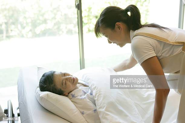 Woman attending to needs of mature patient
