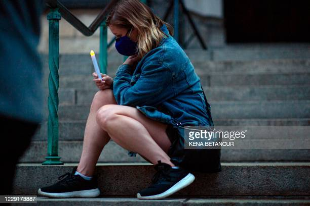 Woman attends a candlelight vigil a procession in tribute to all of the lives affected by the novel coronavirus outside The Cathedral of St. John the...