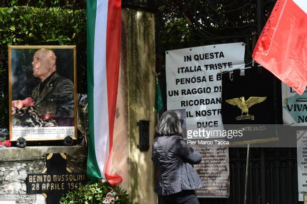 Woman attends a commemoration ceremony for the death of Italian dictator Benito Mussolini and his mistress, Claretta Petacci in front of a headstone...