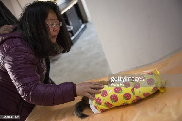 A woman attends a funeral for her pet dog Xiaoxiao who died at the age of 6 months at Wangzai pet cemetery on March 27 2017 in Wuhan Hubei province...