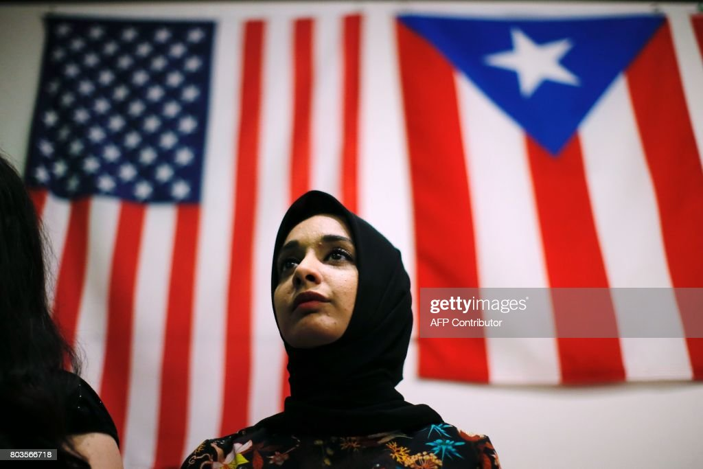 A woman attends a town hall meeting following a rally to protest restrictive guidelines issued by the US on who qualifies as a close familial relationship under the Supreme Court order on the Muslim and refugee ban at Union Square on June 29, 2017, in New York. US President Donald Trump's five-month effort to implement a promised ban on travelers from six mostly Muslim countries and on all refugees takes effect late Thursday, July 29, 2017 as controversy swirls over who qualifies for an exemption based on family ties. ALVAREZ