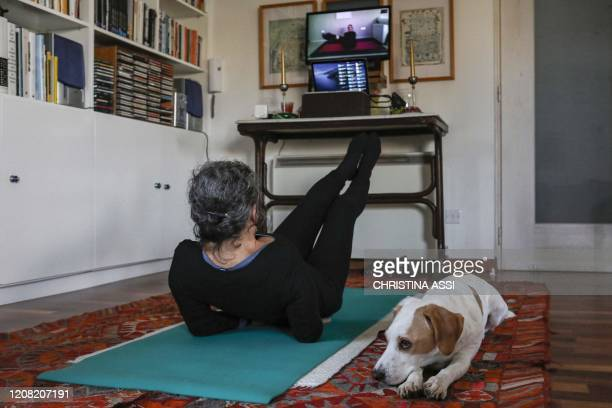 Woman attends an online pilates class as her dog, Elvis, sits next to her during the lesson at home in the Cypriot capital Nicosia on March 23 as...