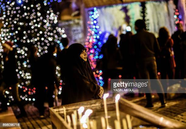 A woman attends Christmas Mass at Saint Antuan Church in the Beyoglu district of Istanbul on December 24 2017 / AFP PHOTO / YASIN AKGUL