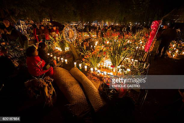 A woman attends to the tomb of a loved one on the eve of the Day of the Dead at the cemetry of Tzintzuntzan in Patzcuaro Michoacan Mexico on November...