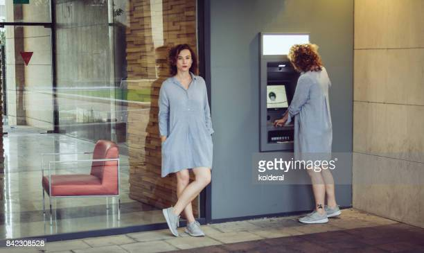 Woman awaiting and withdrawing cash from ATM