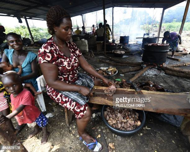 A woman backing a mother breastfeeding her child tries to cut boiled donkey meat to sell to vendors at an abattoir in Ughelli Delta State in southern...