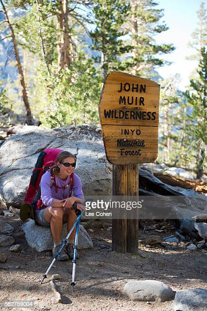 Woman backpacker and wilderness sign
