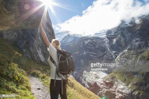 Frau Backpacker lehnt sich an Felsen unterwegs
