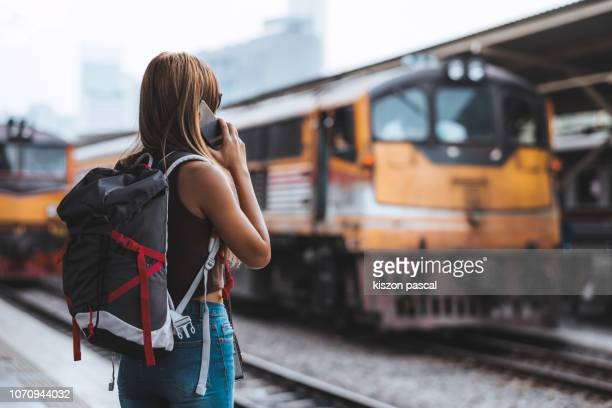 woman backpacker using phone while waiting for her train in rail way station . - passagier stockfoto's en -beelden