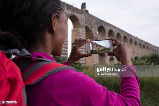 woman backpackers taking picture of an ancient aqueduct in her journey outdoor. - israeli woman stock pictures, royalty-free photos & images
