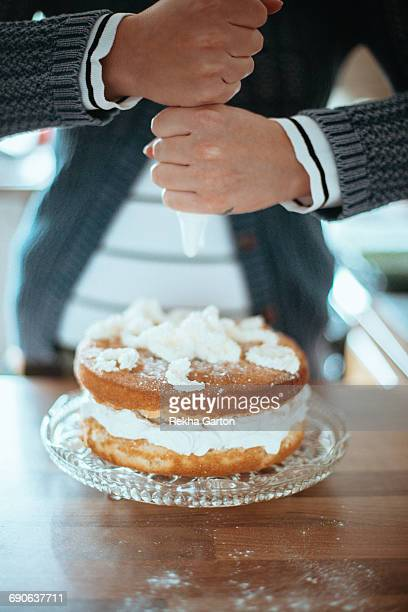 woman badly piping a cake - rekha garton stock pictures, royalty-free photos & images