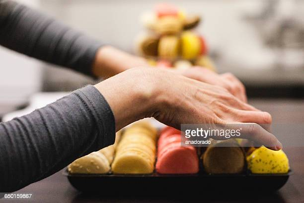 Woman Baker arranging macaroons on a display tray