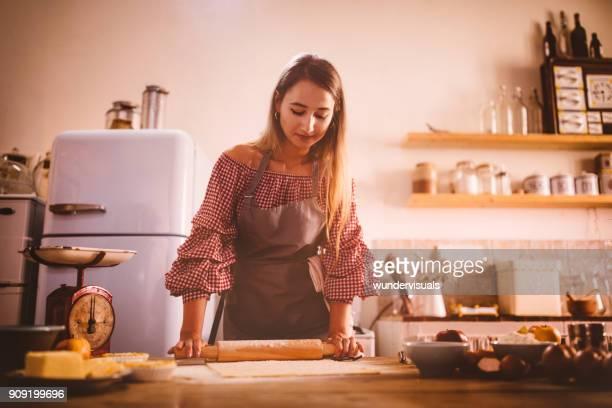 vrouw bakken en deeg met de deegroller rollen in keuken - country christmas stockfoto's en -beelden
