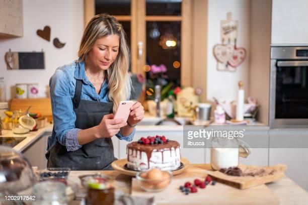 frau backt zu hause: ihren schokoladen-schwammkuchen mit beeren fotografieren - fotohandy stock-fotos und bilder
