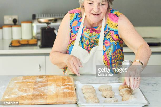 woman baking at home - senior women stock pictures, royalty-free photos & images