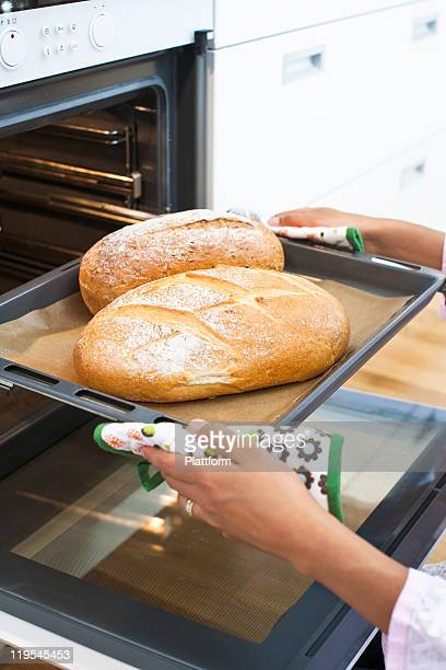 Woman baking bread in kitchen oven