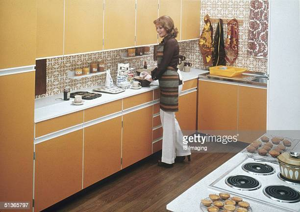 A woman baking cakes in a fitted kitchen circa 1975