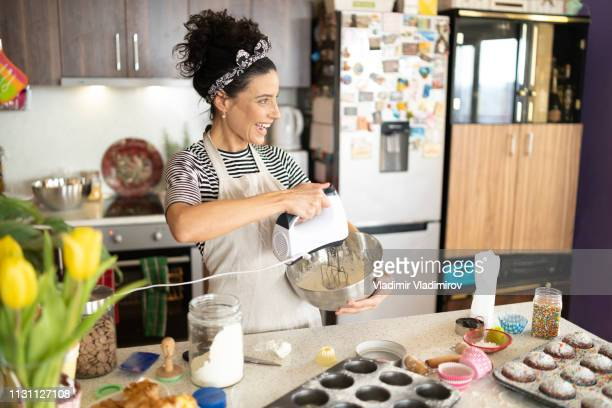 woman baking muffins - decorating a cake stock pictures, royalty-free photos & images