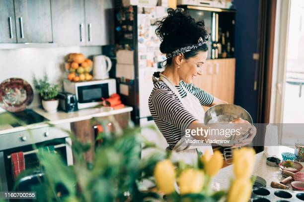 woman baking muffins - one mature woman only stock pictures, royalty-free photos & images