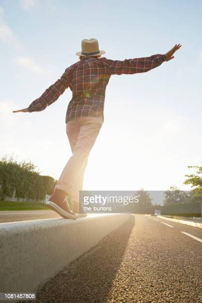 woman balances on a curb - stepping stock pictures, royalty-free photos & images