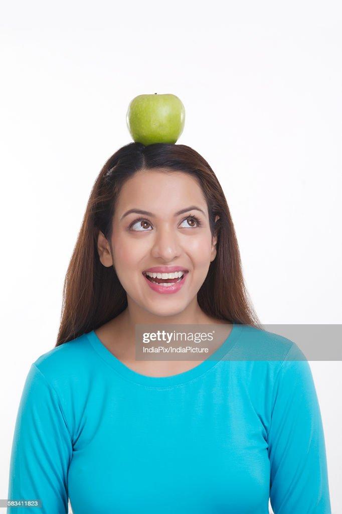 Woman balancing apple on head : Stock Photo