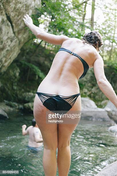 a woman balancing before jumping into a swimming hole in the woods with a waterfall - heshphoto imagens e fotografias de stock