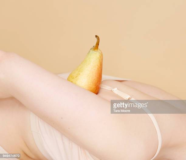woman balancing fruit on body