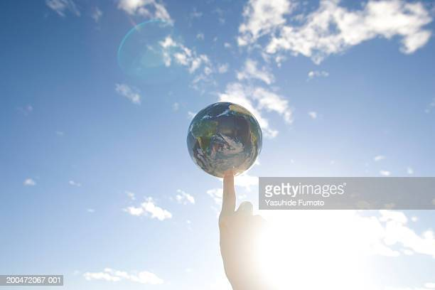 Woman balancing globe on finger, close-up of hand