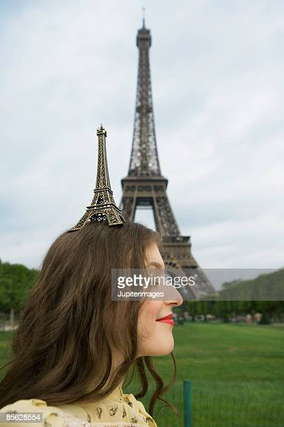 Woman balancing model on head near Eiffel Tower in Paris,  France