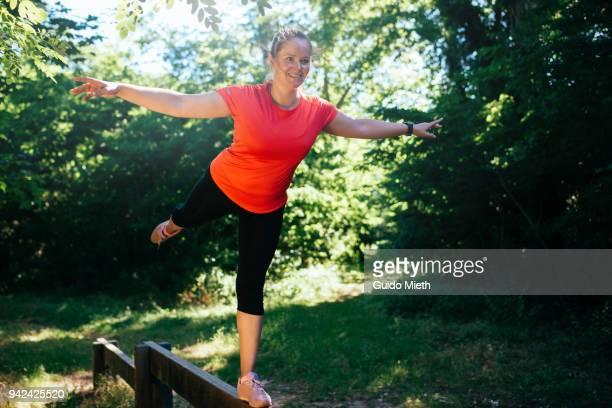 Woman balancing on a bar.