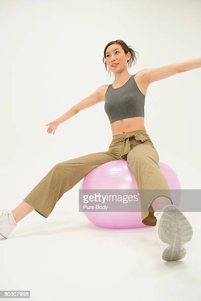 woman balancing on a fitness ball, low angle - 足を開く ストックフォトと画像