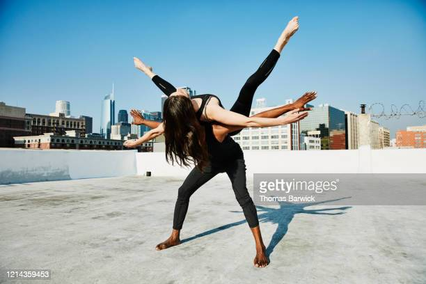 woman balancing on dance partners back while performing on rooftop overlooking city - koordination stock-fotos und bilder
