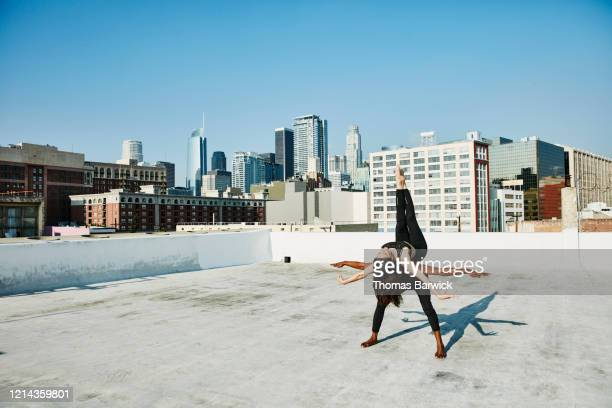 woman balancing on dance partners back while performing on rooftop overlooking city - friendly match stockfoto's en -beelden